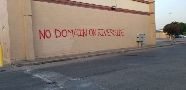 'No Domain On Riverside' written on the wall of a shopping center.