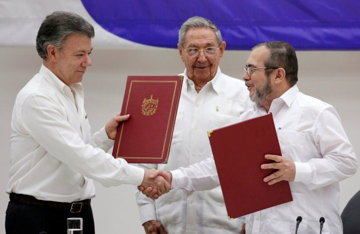 Cuba's President Raul Castro, Colombia's President Juan Manuel Santos and FARC rebel leader Rodrigo Londono react after the signing of a historic ceasefire deal between the Colombian government and FARC rebels in Havana