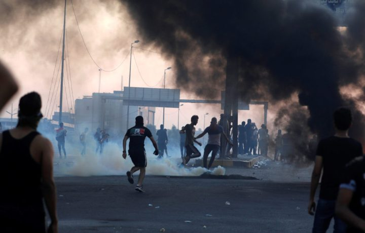 Demonstrators disperse as Iraqi security forces use tear gas during a protest after the lifting of the curfew, following four days of nationwide anti-government protests that turned violent, in Baghdad