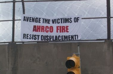 "Banner reads ""Avenge the Victims of AHRCO Fire, Resist Displacement!"""