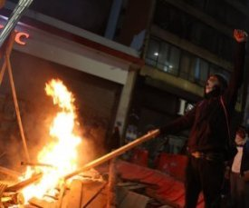 Protester adds fuel toa burning street barricade