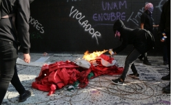 "Masked student burns Mexican Flag, graffiti reads ""UNAM covers-up sexual harassment"""